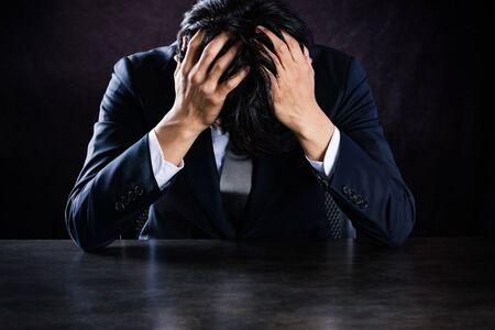 Asian businessman depressed at desk