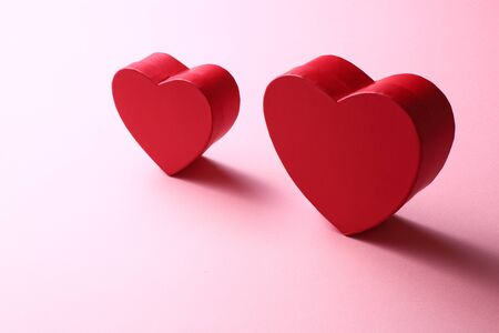 Two red hearts on pink background Stock Photo