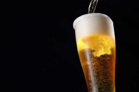 Pouring draft beer on black background