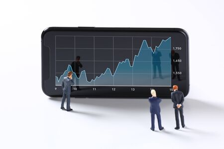 A miniature businessman figure looking at a smartphone screen with a graph