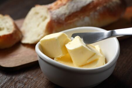 Butter and baguette on the wooden table