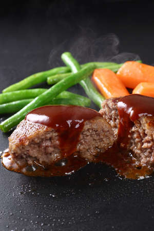 Beef hamburger steak grilled on an iron plate