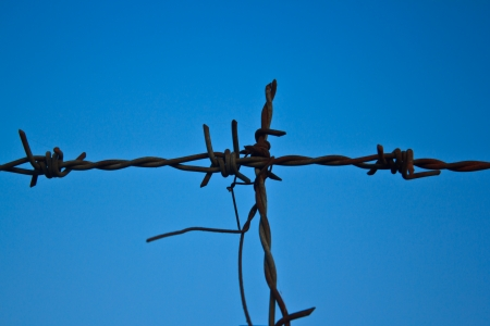 Barb wire fence and blue sky photo