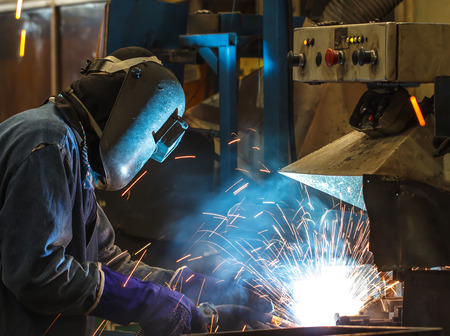 light worker: worker with protective mask welding metal