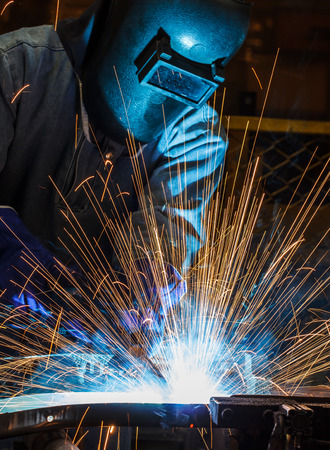 welding worker: worker with protective mask welding metal