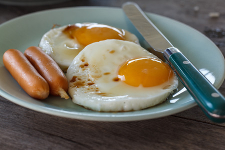 fried eggs: Fried Eggs on a plate (wooden background) Stock Photo