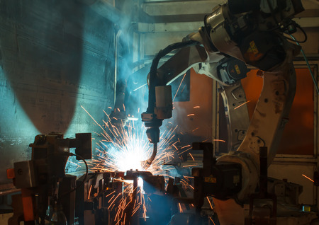 modern manufacturing: robots welding in a car factory