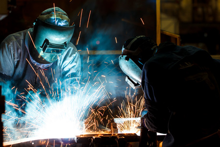 steel making: worker with protective mask welding metal