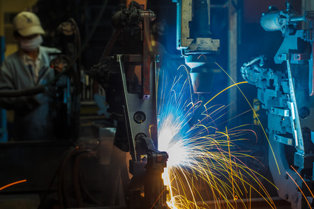 manufacturing: robots welding in a car factory