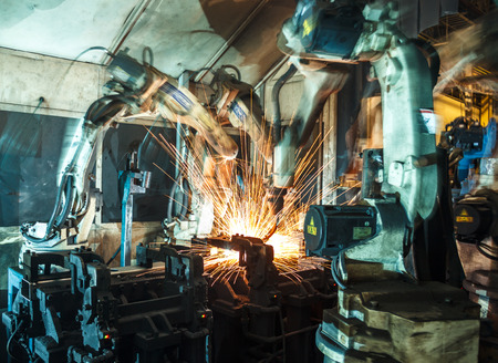 Welding robots represent the movement in the automotive parts industry Imagens