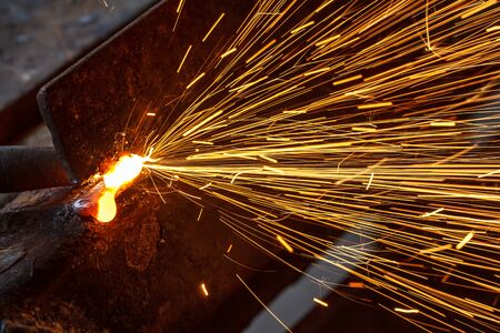 steel worker: Sparks while cutting steel in the factory.
