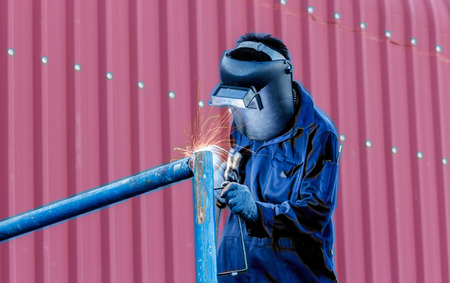welding mask: worker with protective mask welding metal