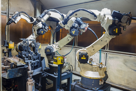 automation: Robots welding team in the automotive parts industry