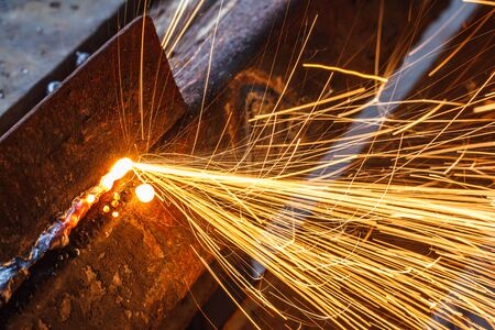 welding worker: Sparks while cutting steel in the factory.