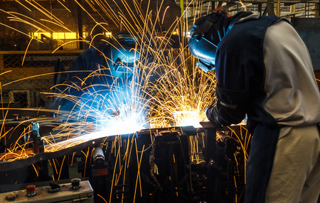 Team worker with protective mask welding.