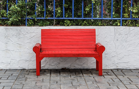 sitting on bench: Red park bench in the park. Stock Photo