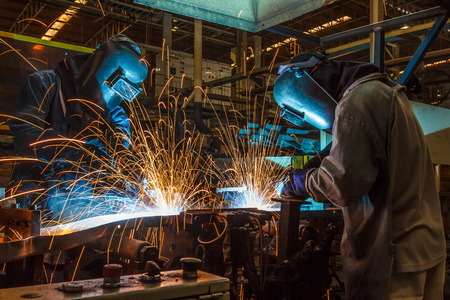 prefabricate: worker with protective mask welding metal