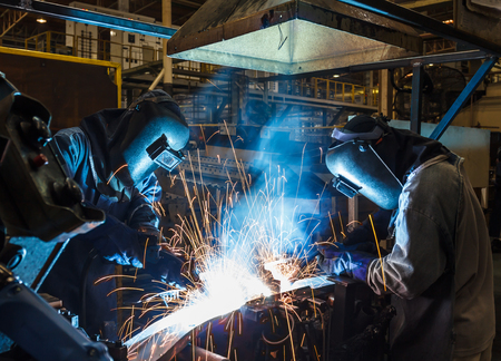 protective mask: worker with protective mask welding metal