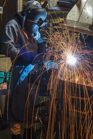 skilled labour: worker with protective mask welding metal in the automotive parts industry