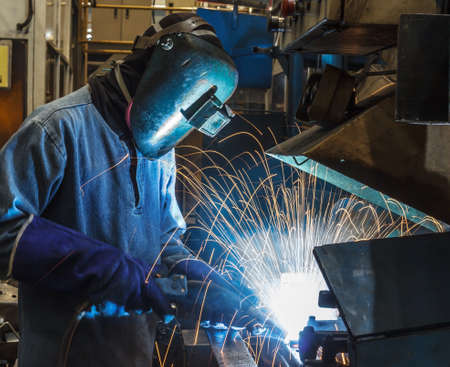 prefabricate: The movement of workers with protective mask welding metal.