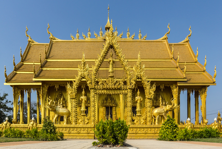 pilgrim journey: Golden temple landmark Buddhist against blue sky in Chachoengsao Province, Thailand.