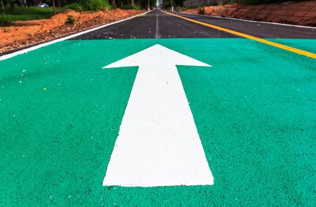 road bike: Bicycle road sign and arrow on bike lane road Stock Photo