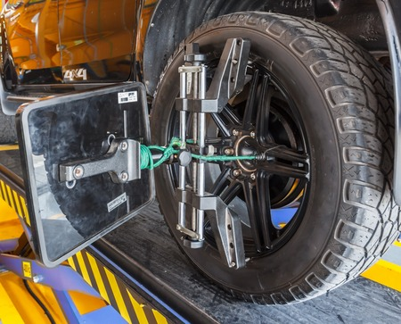 lifting jack: Car wheel fixed with computerized wheel alignment machine clamp