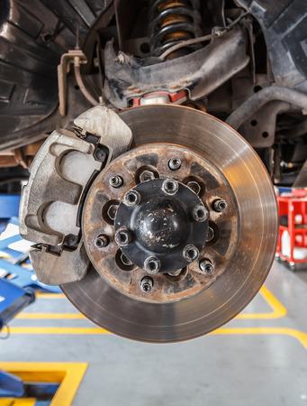 freno de disco delantero en el coche en el proceso de sustitución dañado. Foto de archivo