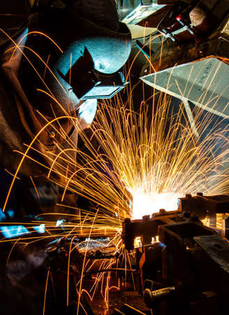 welded: worker with protective mask welding metal