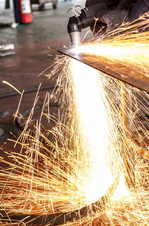 obscured face: manufacturing metal construction by cutting to shape using huge orange sparks