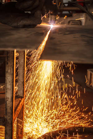manufacturing metal construction by cutting to shape using huge orange sparks
