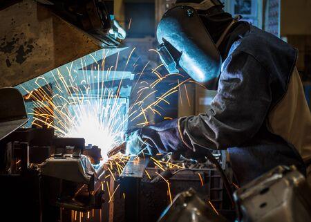 fabricator: Industrial steel worker speeds motion in factory worker with protective mask welding metal