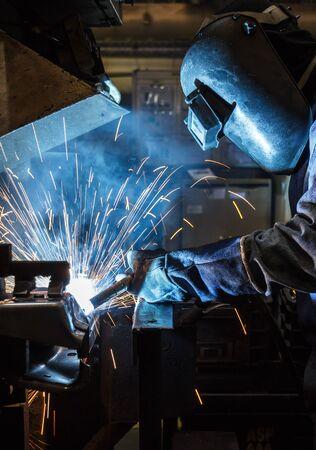 mig: Industrial steel worker speeds motion in factory worker with protective mask welding metal