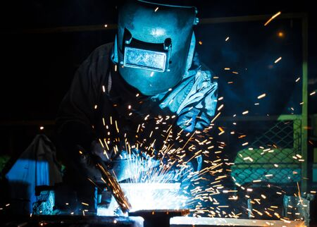 mig: worker with protective mask welding metal