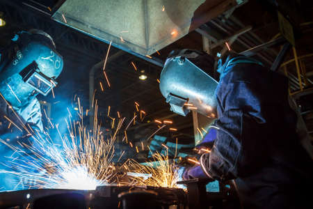 skilled labour: The movement of workers with protective mask welding metal.