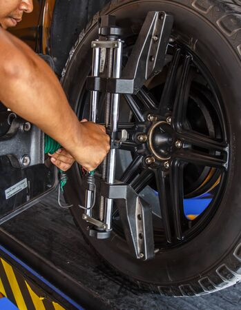 clavados: Car wheel fixed with computerized wheel alignment machine clamp