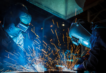 welded: The movement of workers with protective mask welding metal.