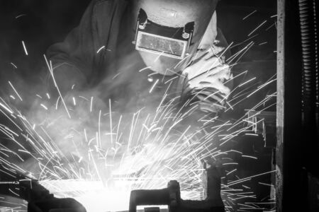 fabricator: worker with protective mask welding metal