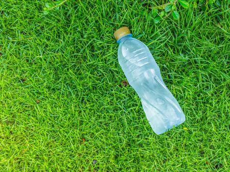 still water: bottle of clear still water in a grass field