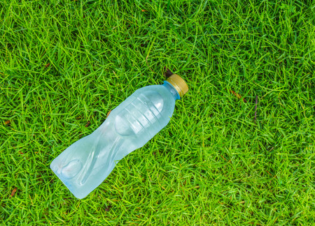 Water small bottle on green grass background