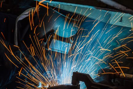 skilled labour: Worker with protective mask welding metal, knowledge to take action Gas welding car industry Stock Photo