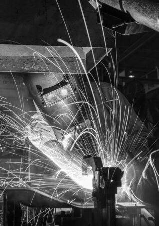 erecting: Worker with protective mask welding metal, knowledge to take action Gas welding car industry Stock Photo