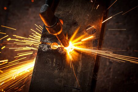 Welder in workshop manufacturing metal construction by cutting to shape using huge orange sparks