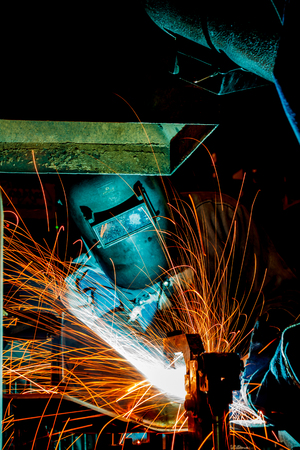 Worker with protective mask welding metal, knowledge to take action Gas welding car industry Standard-Bild
