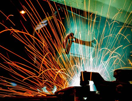prefabricate: Worker with protective mask welding metal, knowledge to take action Gas welding car industry Stock Photo