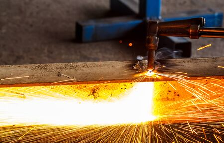 iron man: Welder in workshop manufacturing metal construction by cutting to shape using huge orange sparks