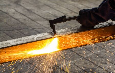 overalls: Welder in workshop manufacturing metal construction by cutting to shape using huge orange sparks