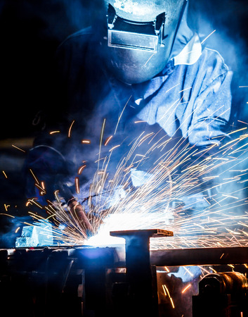 The movement of workers with protective mask welding metal.