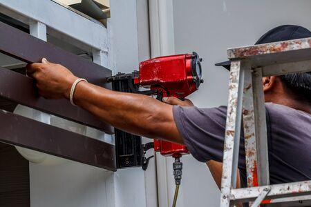 door casing: Gun construction shoot the nails in the wooden wall