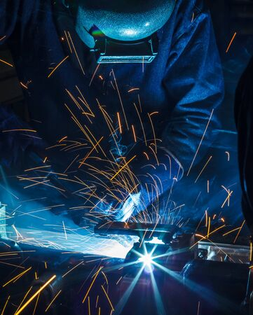 welder is welding steel structure with all safety equipment in factory